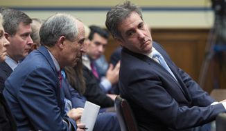 Michael Cohen, right, President Donald Trump's former lawyer, leans back to listen to his lawyer, Lanny Davis of Washington, as he testifies before the House Oversight and Reform Committee, on Capitol Hill, Wednesday in Washington. (AP Photo/Alex Brandon)