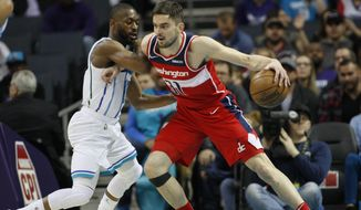 Washington Wizards guard Tomas Satoransky, right, drives into Charlotte Hornets guard Kemba Walker in the first half of an NBA basketball game in Charlotte, N.C., Friday, March 8, 2019. (AP Photo/Nell Redmond)