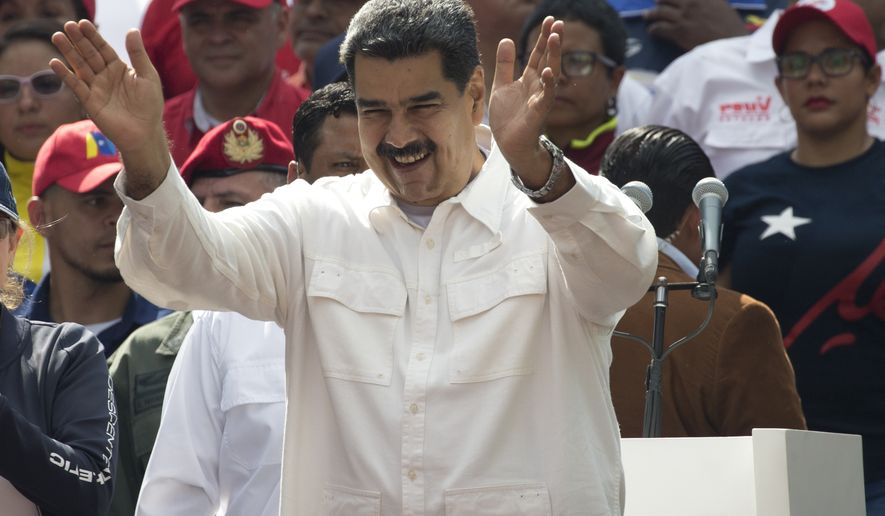 Venezuela's President Nicolas Maduro acknowledges supporters during a government rally in Caracas, Venezuela, Saturday, March 9, 2019.  Demonstrators danced and waved flags on what organizers labeled a day of anti-imperialism in a show of defiance toward the United States, which has imposed oil sanctions on Venezuela in an attempt to oust the president. (AP Photo/Ariana Cubillos)