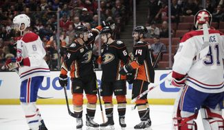 Anaheim Ducks' Troy Terry, center, is congratulated by Cam Fowler, left, and Adam Henrique after he scored a goal against Montreal Canadiens goaltender Carey Price during the second period of an NHL hockey game Friday, March 8, 2019, in Anaheim, Calif. (AP Photo/Jae C. Hong)