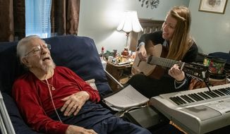 "In this Feb. 4, 2019 photo, Donald Granstaff, 92, sings Louis Armstrong's ""On the Sunny Side of the Street"" at his Princeton, Ky., home with board certified music therapist Kenna Hudgins, a contractor with Pennyroyal Hospice. Hudgins designs Donald's weekly music therapy sessions to help decrease any feelings of isolation. (Michele Vowell/Kentucky New Era via AP)"