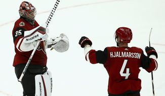 Arizona Coyotes goaltender Darcy Kuemper (35) celebrates his shutout against the Calgary Flames with defenseman Niklas Hjalmarsson (4) at the end of an NHL hockey game Thursday, March 7, 2019, in Glendale, Ariz. The Coyotes won 2-0. (AP Photo/Ross D. Franklin)