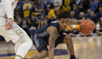 Georgetown guard James Akinjo, right, is guarded by Marquette guard Markus Howard, left, during the second half of an NCAA college basketball game Saturday, March 9, 2019, in Milwaukee. Georgetown beat Marquette 86-84. (AP Photo/Darren Hauck) ** FILE **