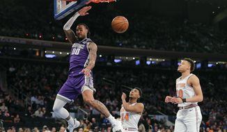 Sacramento Kings center Willie Cauley-Stein (00) dunks the ball ahead of New York Knicks guard Allonzo Trier (14) and forward Kevin Knox (20) during the second quarter of an NBA basketball game, Saturday, March 9, 2019, in New York. (AP Photo/Julie Jacobson)