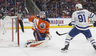 Toronto Maple Leafs' John Tavares (91) watches the puck go past Edmonton Oilers' goalie Anthony Stolarz (32) during the first period of an NHL hockey game Saturday, March 9, 2019, in Edmonton, Alberta. (Jason Franson/The Canadian Press via AP)