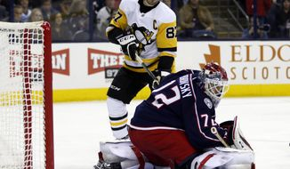 Columbus Blue Jackets goalie Sergei Bobrovsky, right, of Russia, makes a stop against Pittsburgh Penguins forward Sidney Crosby during the first period of an NHL hockey game in Columbus, Ohio, Saturday, March 9, 2019. (AP Photo/Paul Vernon)