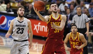 USC forward Nick Rakocevic, right, drives past Colorado forward Lucas Siewert for a basket in the first half of an NCAA college basketball game Saturday, March 9, 2019, in Boulder, Colo. (AP Photo/David Zalubowski)