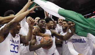 Seton Hall forward Michael Nzei, center, celebrates with teammates and a Nigerian flag after Seton Hall Seton Hall defeated Villanova 79-75 in an NCAA college basketball game, Saturday, March 9, 2019, in Newark, N.J. It was Nzei's final regular season game at the Prudential Center, the team's home arena as he is a senior. (AP Photo/Kathy Willens)