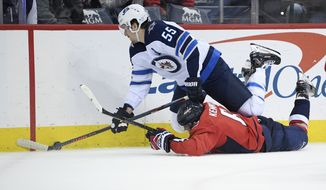 Winnipeg Jets center Mark Scheifele (55) battles for the puck against Washington Capitals defenseman Michal Kempny (6), of the Czech Republic, during the second period of an NHL hockey game, Sunday, March 10, 2019, in Washington. (AP Photo/Nick Wass)