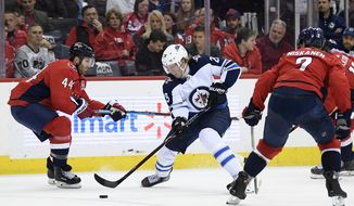 Winnipeg Jets right wing Patrik Laine (29), of Finland, skates with the puck against Washington Capitals defenseman Brooks Orpik (44) and defenseman Matt Niskanen (2) during the second period of an NHL hockey game, Sunday, March 10, 2019, in Washington. The Capitals won 3-1. (AP Photo/Nick Wass) ** FILE **
