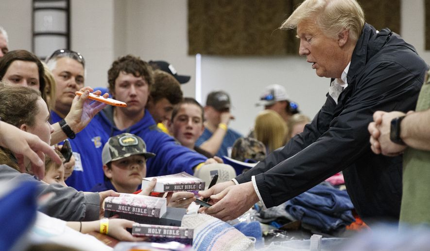 President Donald Trump greets people, signing Bibles and other items, as he visits Providence Baptist Church in Smiths Station, Ala., Friday, March 8, 2019, as he tours areas where tornadoes killed 23 people in Lee County, Ala. (AP Photo/Carolyn Kaster)