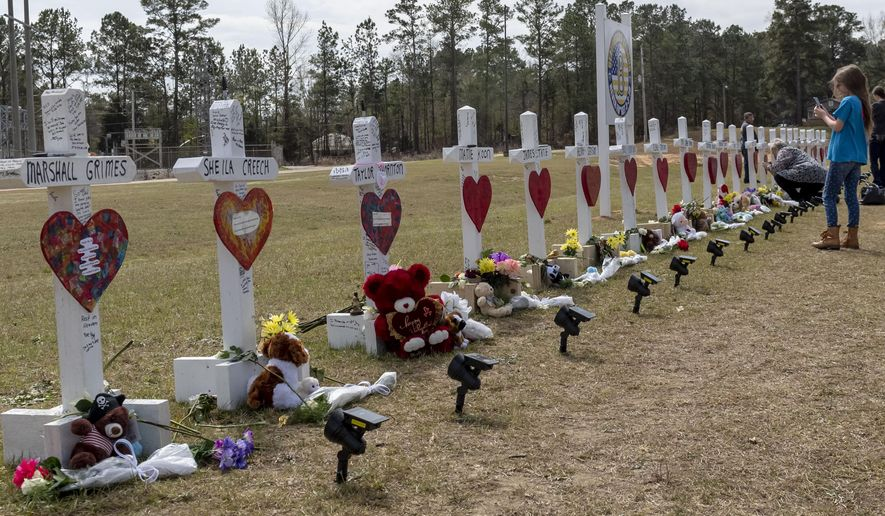 Katie Nobles photographs crosses representing the 23 lives lost in the tornado that hit the Beauregard community on March 3, to share with her friend who was injured in the storm and lost loved ones, Sunday, March 10, 2019, at Providence Baptist Church in Beauregard, Ala. Nobles' friend Kayla Grimes lost family members to the storm and is still recovering from serious injuries in a Birmingham hospital. (AP Photo/Vasha Hunt)