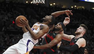 Phoenix Suns forward Josh Jackson, left, prepares to shoot as Portland Trail Blazers forward Maurice Harkless, center, and center Jusuf Nurkic, right, defend during the first half of an NBA basketball game in Portland, Ore., Saturday, March 9, 2019. (AP Photo/Steve Dipaola)