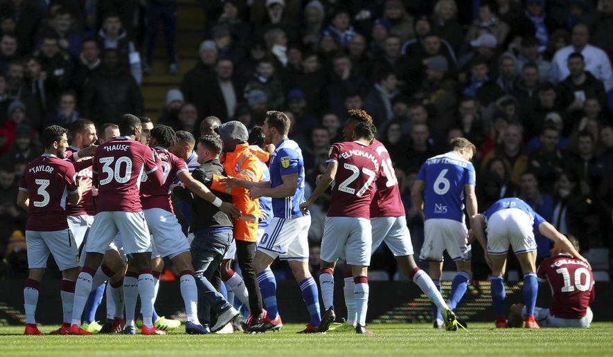 A fan is removed after attacking Aston Villa's Jack Grealish, right, on the pitch during the Sky Bet Championship soccer match at St Andrew's Trillion Trophy Stadium, Birmingham, England, Sunday March 10, 2019. (Nick Potts/PA via AP)