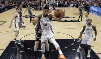 Milwaukee Bucks forward Giannis Antetokounmpo (34) pulls down a rebound in front of San Antonio Spurs center Jakob Poeltl (25) during the first half of an NBA basketball game, in San Antonio, Sunday, March 10, 2019. (AP Photo/Eric Gay)