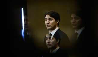 Prime Minister Justin Trudeau is seen through a beveled pane of glass in a door as he takes part in a news conference in Iqaluit, Nunavut, Canada. (Sean Kilpatrick/The Canadian Press via AP, File)