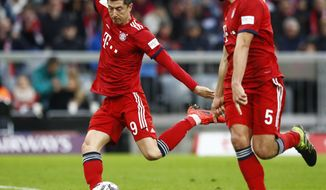 Bayern's Robert Lewandowski, left, kicks the ball during the German Bundesliga soccer match between FC Bayern Munich and VfL Wolfsburg in Munich, Germany, Saturday, March 9, 2019. Robert Lewandowski has become the outright top-scoring foreign player in Bundesliga history. (AP Photo/Matthias Schrader)