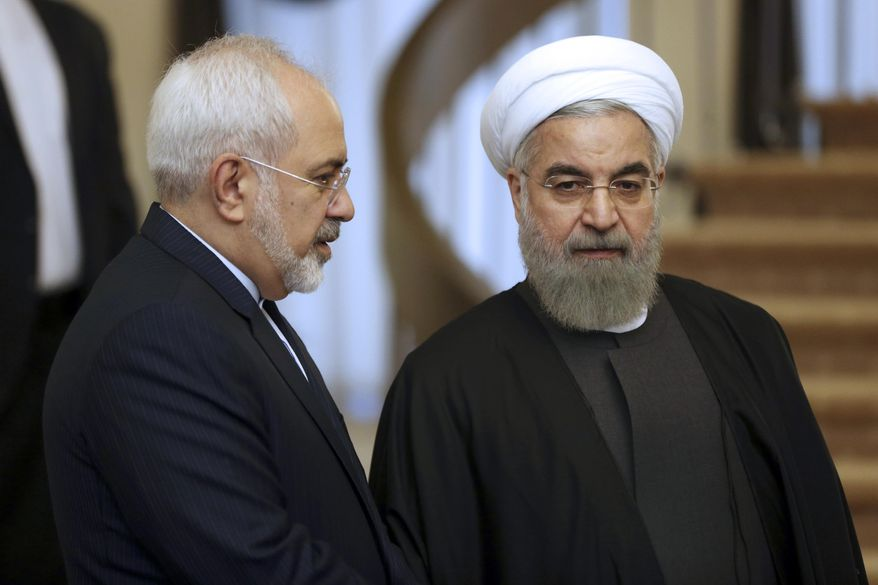 In this Nov. 24, 2015, file photo, Iranian President Hassan Rouhani, right, listens to his Foreign Minister Mohammad Javad Zarif prior to a meeting in Tehran, Iran. Rouhani is planning to make his first official visit to Iraq Monday, March 11, 2019, as he faces mounting pressure from hard-liners at home in the wake of the unravelling of the nuclear deal under the Trump administration. (AP Photo/Vahid Salemi, File)