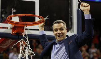 Virginia head coach Tony Bennett holds a piece of the net after a victory over Louisville after an NCAA college basketball game in Charlottesville, Va., Saturday, March 9, 2019. (AP Photo/Steve Helber) **FILE**