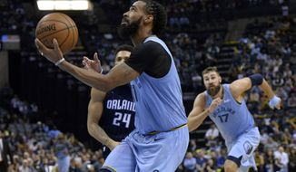 Memphis Grizzlies guard Mike Conley drives to the basket ahead of Orlando Magic center Khem Birch (24) and Grizzlies center Jonas Valanciunas (17) in the second half of an NBA basketball game Sunday, March 10, 2019, in Memphis, Tenn. (AP Photo/Brandon Dill)