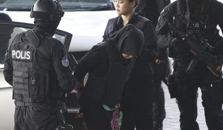 Indonesian Siti Aisyah, center, is escorted by police as she arrives at Shah Alam High Court in Shah Alam, Malaysia, Monday, March 11, 2019. The trial of two Southeast Asian women charged with murdering Kim Jong Nam, North Korean leader's half brother, resumed Monday after months of delay, with the Vietnamese suspect taking the stand to begin her defense. (AP Photo/Yam G-Jun)