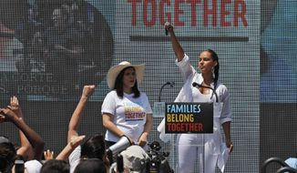 FILE - In this June 30, 2018 file photo, America Ferrera, left, with Alicia Keys, attends a protest against the Trump administration's approach to illegal border crossings and separation of children from immigrant parents in Lafayette Square across from the White House in Washington. After paying a weekend visit to Central Americans stuck on the Mexican side of the border with the United States, Ferrera said Sunday, March 10, 2019, that she was enjoying first-time motherhood last June when images of migrant children being separated from their parents by U.S. officials began to emerge. She has led a small group of like-minded artists on a visit to migrants waiting in the Mexican border city of Tijuana for a chance to apply for asylum in the U.S. (AP Photo/Alex Brandon, File)