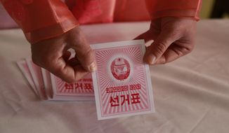 An electoral worker shows a ballot during the election at a polling station in Pyongyang, North Korea, Sunday, March 10, 2019. Millions of North Korean voters, including leader Kim Jong Un, are going to the polls to elect roughly 700 members to the national legislature. In typical North Korean style, voters are presented with just one state-sanctioned candidate per district and they cast ballots to show their approval or, very rarely, disapproval. (AP Photo/Dita Alangkara)