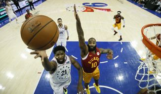 Philadelphia 76ers' Joel Embiid (21) goes up for a shot past Indiana Pacers' Kyle O'Quinn (10) during the first half of an NBA basketball game, Sunday, March 10, 2019, in Philadelphia. (AP Photo/Matt Slocum)