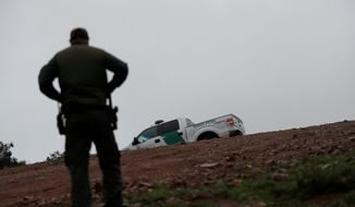 """""""Hundreds of man hours are wasted each day at a time of crisis on the border,"""" said the leaders of the National ICE Council in a letter. Border Patrol agent Vincent Pirro looks on near where a border wall ends that separates the cities of Tijuana, Mexico, and San Diego, Tuesday, Feb. 5, 2019, in San Diego. President Donald Trump is expected to speak about funding for a wall along the U.S.-Mexico border during his State of the Union address Tuesday. (AP Photo/Gregory Bull) (Associated Press)"""