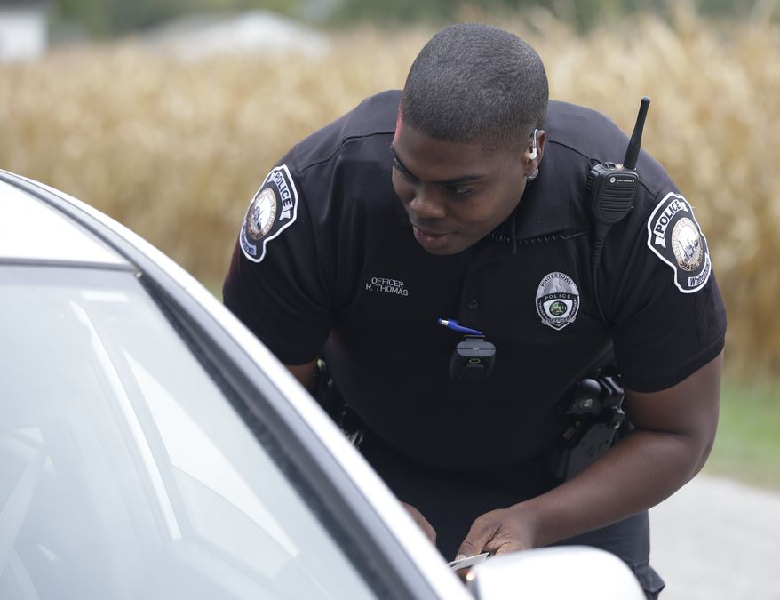 A police officer makes a traffic stop in Whitestown, Ind. (AP Photo/Darron Cummings)