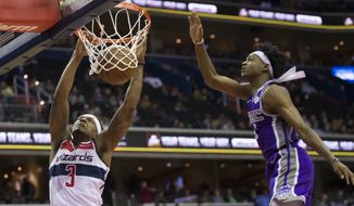 Washington Wizards guard Bradley Beal, left, dunks the ball past Sacramento Kings guard De'Aaron Fox during the second half of an NBA basketball game Monday, March 11, 2019, in Washington. The Wizards won 121-115. (AP Photo/Alex Brandon) **FILE**