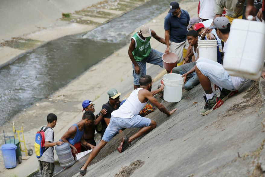 People collect water falling from a leaking pipeline on the bank of the Guaire River during rolling blackouts, which affects access to running water, in Caracas, Venezuela, Monday, March 11, 2019. The blackout has intensified the toxic political climate, with opposition leader Juan Guaido blaming alleged government corruption and mismanagement and President Nicolas Maduro accusing his U.S.-backed adversary of sabotaging the national grid. (AP Photo/Fernando Llano)