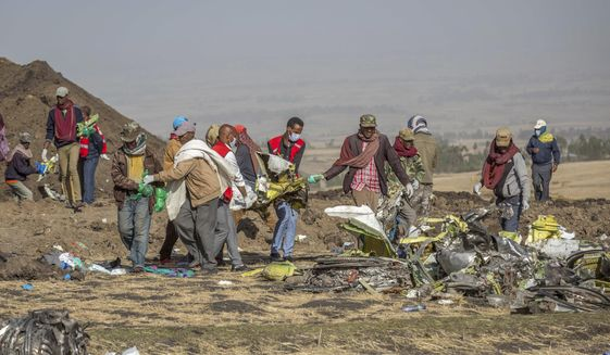 Rescuers work at the scene of an Ethiopian Airlines flight crash near Bishoftu, or Debre Zeit, south of Addis Ababa,  Ethiopia, Monday, March 11, 2019. A spokesman says Ethiopian Airlines has grounded all its Boeing 737 Max 8 aircraft as a safety precaution, following the crash of one of its planes in which 157 people were killed. (AP Photo/Mulugeta Ayene)