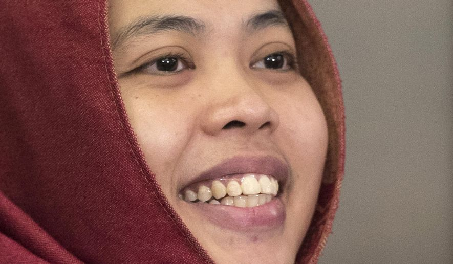 Indonesian Siti Aisyah smiles after a press conference at Indonesian Embassy in Kuala Lumpur, Malaysia, Monday, March 11, 2019. The Indonesian woman held two years on suspicion of killing North Korean leader's half brother Kim Jong Nam was freed from custody Monday after prosecutors unexpectedly dropped the murder charge against her. (AP Photo/Vincent Thian)