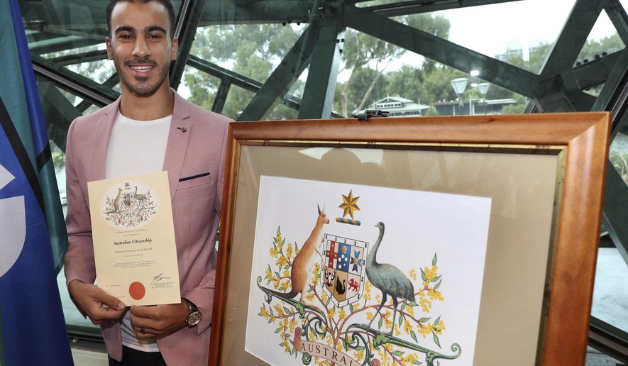 Hakeem al-Araiby, a former Bahraini international soccer player and refugee displays his certificate after becoming an Australian citizen, four weeks after escaping extradition to his homeland during a much-publicized detention in a Thai prison, in Melbourne, Tuesday, March 12, 2019. Al-Araiby, who fled Bahrain citing political repression, had lived under refugee status in Australia for more than a year until detained in Bangkok in November while on holiday. (David Crosling/AAP Image via AP)