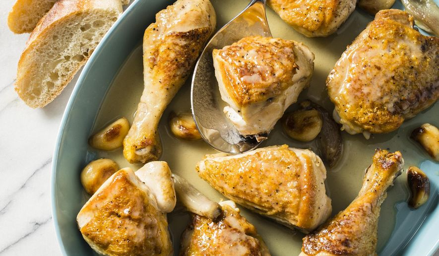 """This undated photo provided by America's Test Kitchen in March 2019 shows Chicken With 40 Cloves Of Garlic. The recipe appears in the cookbook """"How to Braise Everything."""" (Steve Klise/America's Test Kitchen via AP)"""