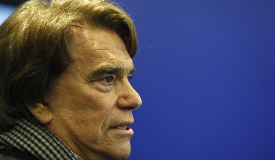 FILE - In this March 12, 2014 file photo, French tycoon Bernard Tapie speaks with the media in Marseille, France. Tapie faces a criminal trial over a fraudulent 404 million-euro ($450 million today) arbitration package linked to his sale of sportswear company Adidas in the 1990s. Tapie and five others were due in court in Paris on Monday, March 11, 2019. (AP Photo/Claude Paris, File)