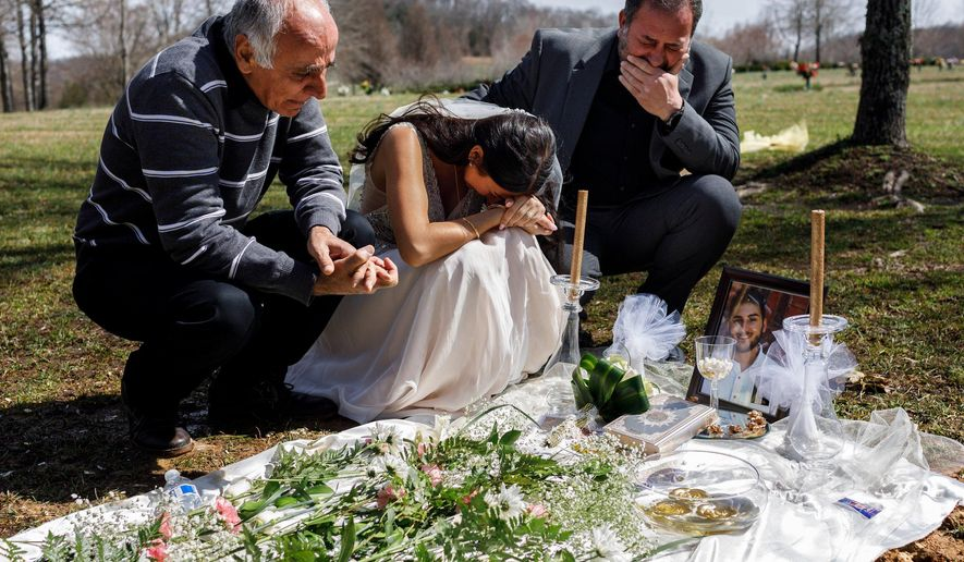 Clad in a wedding dress, Sara Baluch, center, mourns with her father Masoud Baluch, left, and her fiance's father Mohssen Sharifi while visiting the grave of her fiance, Mohammad Sharifi, on Sunday, March 10, 2019, the day after they were supposed to be married, at Harpeth Hills Memory Gardens in Nashville, Tenn. Sharifi, a UTC student, was shot and killed two weeks before their wedding by a man to whom he was trying to sell an Xbox. (Doug Strickland/Chattanooga Times Free Press via AP)
