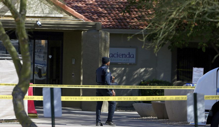 A Phoenix Police Department officer walks past the main entrance of the Hacienda HealthCare facility after a shooting in the parking area Monday, March 11, 2019, in Phoenix.  (AP Photo/Ross D. Franklin)