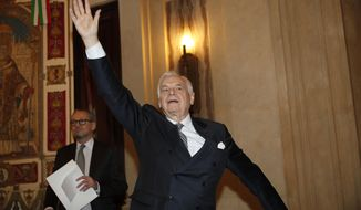 La Scala theater general manager Alexander Pereira waves as he arrives for a the press conference, in Milan, Italy, Monday, March 11, 2019. Italy's premier opera house, La Scala in Milan, is under fire over a proposal to grant a board seat to Saudi Arabia's culture minister with the promise of 15 million euros ($16.8 million) in new funding. (AP Photo/Antonio Calanni)