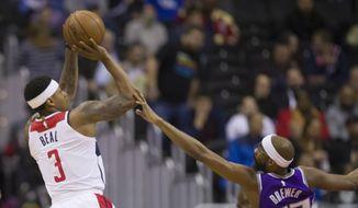 Washington Wizards guard Bradley Beal (3) shoots over Sacramento Kings guard Corey Brewer (33) during the first half of an NBA basketball game Monday, March 11, 2019, in Washington. (AP Photo/Alex Brandon)