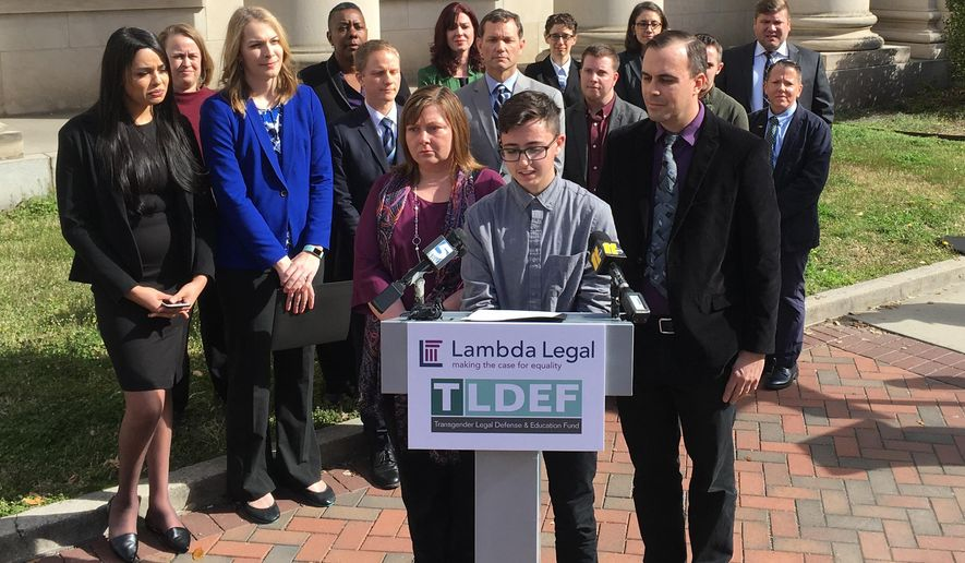 Connor Thonen-Fleck addresses reporters while his parents stand by his side on Monday March 11, 2019, in Durham, North Carolina at the announcement of a lawsuit against North Carolina officials over how the state health plan is run. The lawsuit argues that North Carolina's state health plan for state employees discriminates by not covering hormone treatment and surgery for transgender people. (AP Photo/ Jonathan Drew)