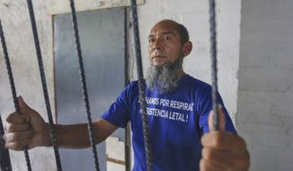 Alex Vanegas holds on to the iron bars he had installed on the porch of his apartment to symbolize his home arrest in Managua, Nicaragua, Tuesday, March 5, 2019. Grasping the iron bars, Vanegas is taken back to the dark prison cells where he spent the previous four months talking to fellow inmates through holes in the walls that also let in rats, scorpions and cockroaches, arrested for protesting against the government of President Daniel Ortega. (AP Photo/Alfredo Zuniga)