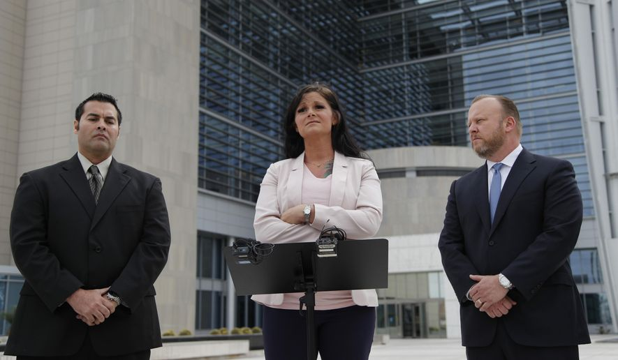 Jennifer Glover, a former security guard at the Nevada National Security Site, center, speaks at a news conference beside Gus Redding, left, and attorney Jay Ellwanger, Monday, March 11, 2019, in Las Vegas. Glover is suing her former employer over allegations she was sexually assaulted and harassed by colleagues and then retaliated against for reporting the incidents. Redding, a former coworker, says he was harassed and retaliated against for cooperating in the investigation. (AP Photo/John Locher)