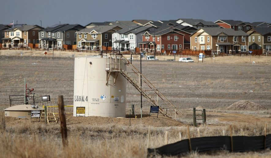 In this Feb. 28, 2019, photograph, a storage tank stands near a well pad located in a field near a housing development in Broomfield, Colo. Frustrated residents of a Denver suburb say state law is forcing them to participate in a major oil and gas drilling project against their wishes, so they launched legal challenges with potentially significant consequences for the industry. Backed by a federal judge, they have a chance this week to ask state regulators to block multiple wells planned within about 1,300 feet (400 meters) of homes in the city of Broomfield. (AP Photo/David Zalubowski)