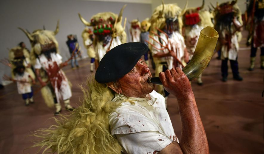 """A man plays a horn as """"momotxorros """" take part in a carnival wearing typical attire, in Alsasua, northern Spain, Tuesday, March 5, 2019. During the carnival """"momotxorros"""" characters, who seem to have been resurrected from a prehistoric ritual, come out onto the streets wearing horns and hiding their faces under headscarves while dressed in a white sheet stained with blood. (AP Photo/Alvaro Barrientos)"""