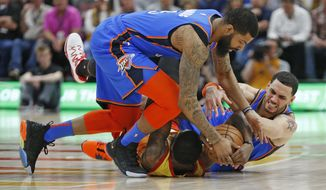 Utah Jazz forward Royce O'Neale, bottom, battles for the ball against Oklahoma City Thunder's Abdel Nader, right, and Markieff Morris, top, in the first half during an NBA basketball game Monday, March 11, 2019, in Kearns, Utah. (AP Photo/Rick Bowmer)