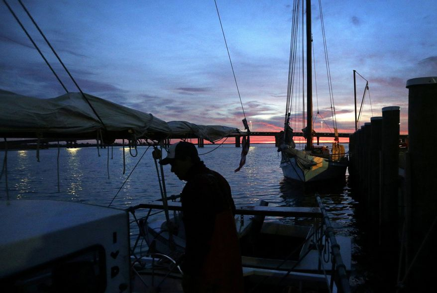 FILE - In this Dec. 20, 2013 file photo, Capt. David Whitelock prepares for a day of oyster dredging on the skipjack Hilda M. Willing as the sun begins to rise over Deal Island, Md. President Donald Trump's 2020 budget released Monday, March 11, 2019 calls for 90 percent cuts in spending on programs for the Great Lakes and Chesapeake Bay. It would eliminate funding for other waterways including the Gulf of Mexico, South Florida, San Francisco Bay and Puget Sound. Trump has sought similar reductions in past budgets but Congress has rejected them. (AP Photo/Patrick Semansky, File)