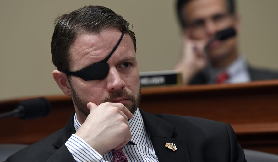Rep. Dan Crenshaw, R-Texas, left, listens as Office of Management and Budget Acting Director Russell Vought testifies before the House Budget Committee on Capitol Hill in Washington, Tuesday, March 12, 2019, during a hearing on the fiscal year 2020 budget. (AP Photo/Susan Walsh)