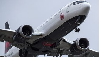 """An Air Canada Boeing 737 Max 8 aircraft arriving from Toronto prepares to land at Vancouver International Airport, in Richmond, British Columbia on Tuesday, March 12, 2019. Canadian Transport Minister Marc Garneau says """"all options are on the table"""" with regard to the country's fleet of Boeing 737 Max 8 aircraft but says the government currently has no plans to order the grounding of the plane. (Darryl Dyck/The Canadian Press via AP)"""